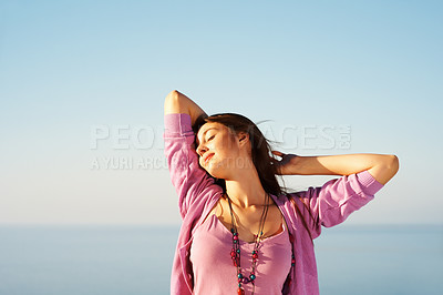 Buy stock photo Beautiful young female standing against sky and enjoying the sunny weather with hands behind head