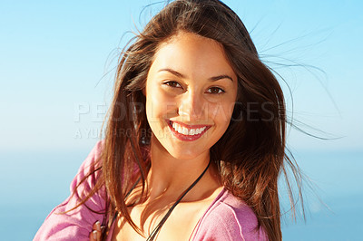 Buy stock photo Closeup of young female standing against sky and giving you cute smile