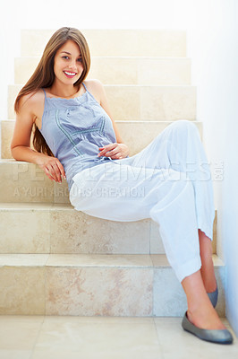 Buy stock photo Full length of attractive young woman sitting casually on the staircase