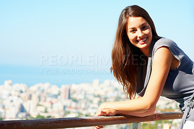Buy stock photo Portrait of smiling young woman leaning on balcony - copyspace