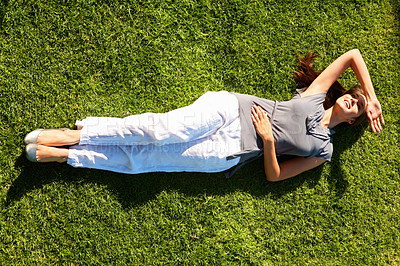 Buy stock photo Full length of pretty young woman lying on grass and shielding her eyes