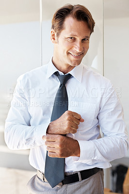 Buy stock photo Portrait of a smiling young businessman adjusting his cuffs