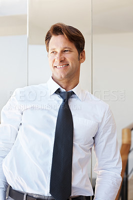Buy stock photo Portrait of a successful young businessman standing and looking away