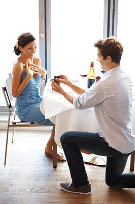 Buy stock photo Handsome young man proposing with an engagement ring to his love in a restaurant
