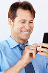Happy businessman texting form his cellphone