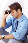 Thoughtful young businessman sitting and holding cellphone