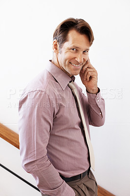 Buy stock photo Portrait of a young male executive on staircase using mobile phone
