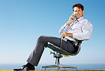 Businessman sitting on chair and using cellphone - Outdoor