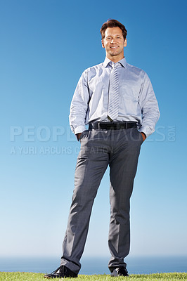 Buy stock photo Portrait of a happy male executive with his hands in pocket standing on grass against sky - Outdoor