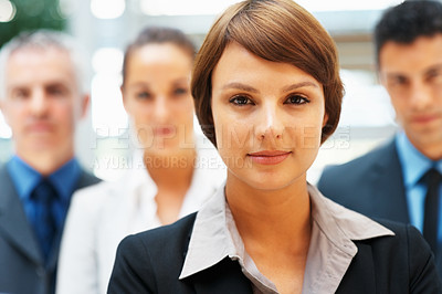 Buy stock photo Focus on female executive with colleagues in background
