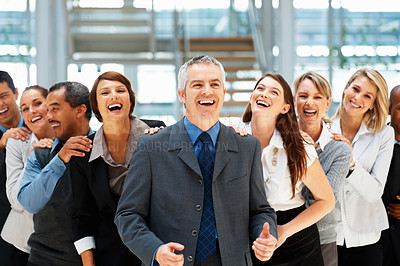 Buy stock photo Group of executives laughing while resting hands on each others shoulders