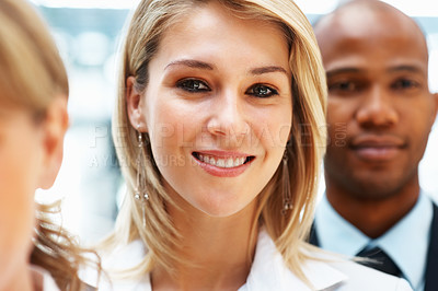 Buy stock photo Focus on pretty woman standing next to colleagues
