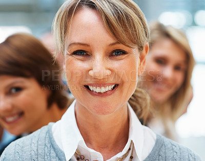 Buy stock photo Closeup of businesswoman with colleagues smiling behind her