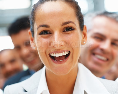 Buy stock photo Pretty businesswoman laughing with smiling team behind her