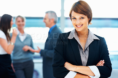 Buy stock photo Young female executive standing with arms folded and colleagues in distance