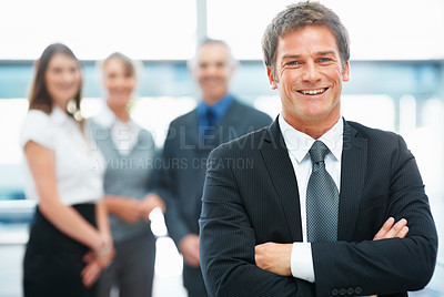 Buy stock photo Confident Male executive smiling with colleagues in background