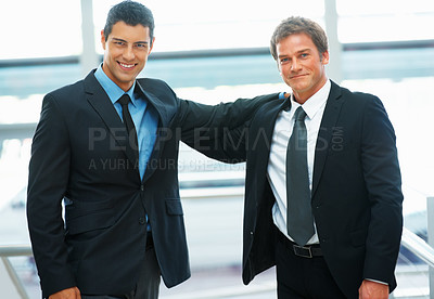 Buy stock photo Two businessmen standing with arm on each others shoulder