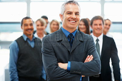 Buy stock photo Confident senior executive standing in front of team