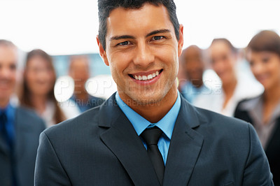 Buy stock photo Closeup of handsome executive smiling with team in background