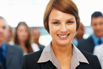 Buy stock photo Closeup of young businesswoman with peers in background