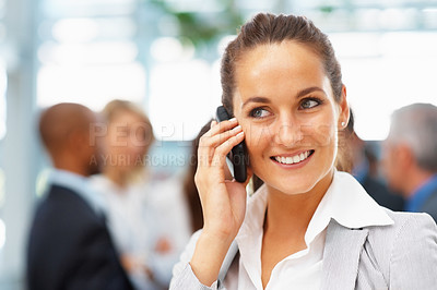 Buy stock photo Female executive having a phone conversation with colleagues in background