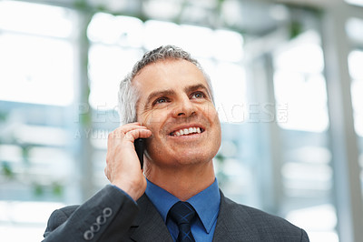 Buy stock photo Senior businessman holding cell phone and smiling indoors
