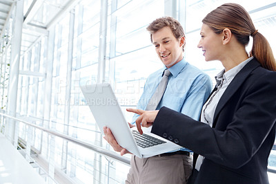 Buy stock photo Young businesspeople sharing a laptop together