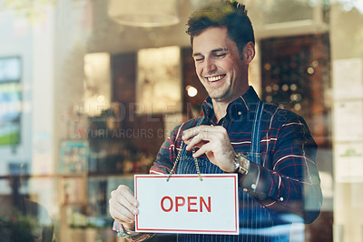 Buy stock photo Shot of a smiling young man hanging up an open sign in a shop window