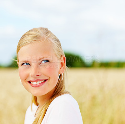 Buy stock photo Closeup of a pretty blond woman smiling at a field