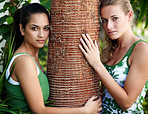 Beautiful teenage women holding a tree bark in a park