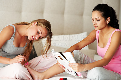 Buy stock photo Portrait of a pretty young woman applying nail polish to a friend's toenails while she reads a magazine