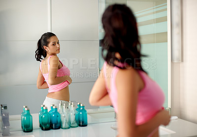 Buy stock photo Portrait of a cute young woman checking her waist in the bathroom mirror