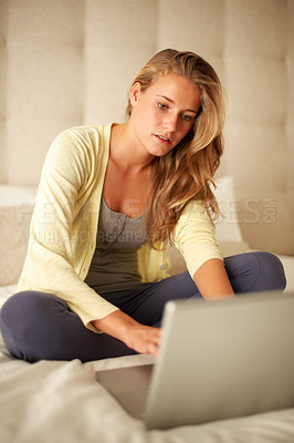 Buy stock photo Portrait of a lovely young woman using on laptop while sitting on the bed at home