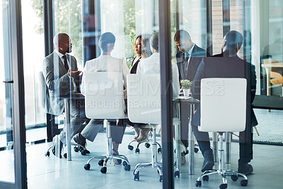 Buy stock photo Shot of a team of professionals having a meeting in the boardroom at work