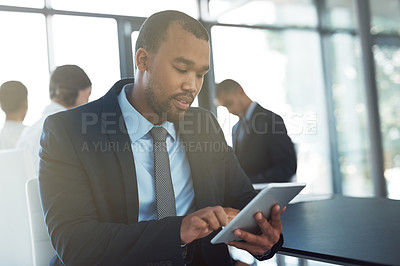 Buy stock photo Shot of a young businessman using a digital tablet during a meeting at work