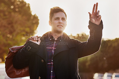 Buy stock photo Shot of a handsome young man hailing a cab