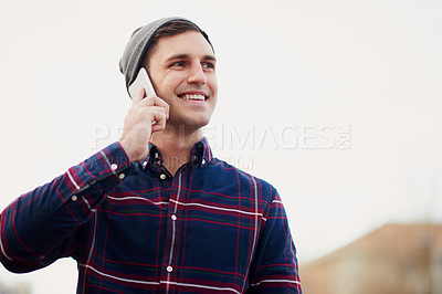 Buy stock photo Shot of a handsome young man talking on his cellphone while walking through the city