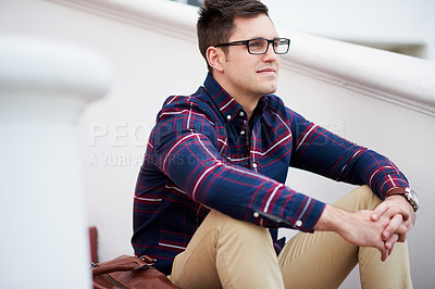 Buy stock photo Shot of a handsome young man sitting on some steps outside