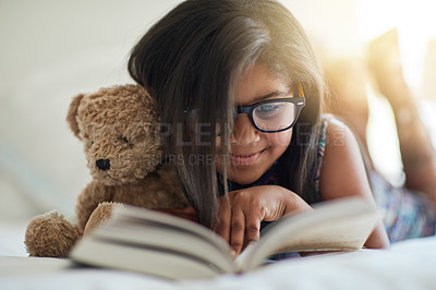 Buy stock photo Shot of a cute little girl reading a book in her bedroom with her teddybear by her side