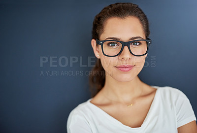 Buy stock photo Studio portrait of an attractive and confident young woman posing against a dark background