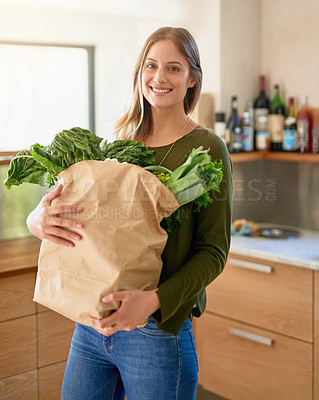 Buy stock photo Portrait of a smiling young woman standing in her kitchen carrying a paper bag full of groceries