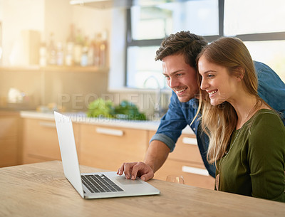 Buy stock photo Shot of a smiling young couple using laptop on their kitchen counter at home