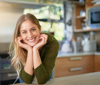 Buy stock photo Portrait of a smiling young woman leaning on her kitchen counter at home