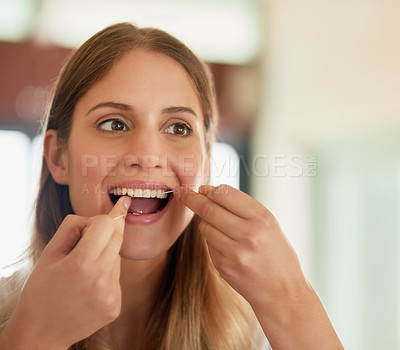 Buy stock photo Cropped shot of a young woman flossing her teeth at home