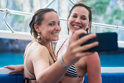 Buy stock photo Cropped shot of two young woman taking a selfie while on holiday