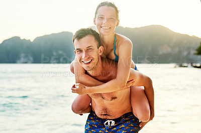 Buy stock photo Portrait of a young couple enjoying the day at the beach