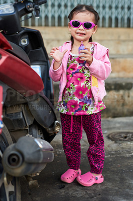 Buy stock photo Portrait of an adorable little girl standing alongside a scooter outside