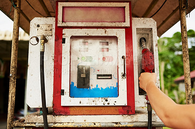 Buy stock photo Cropped shot of a man using an old pump at a gas station