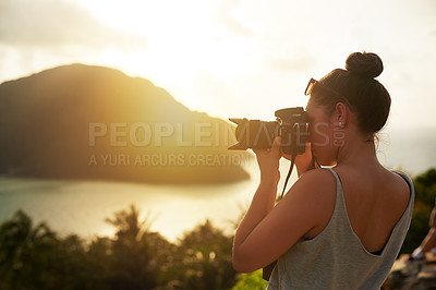 Buy stock photo Shot of a young woman photographing a tropical view while on holiday