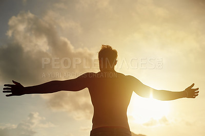 Buy stock photo Rearview shot of a young man with open arms silhouetted against a sunset